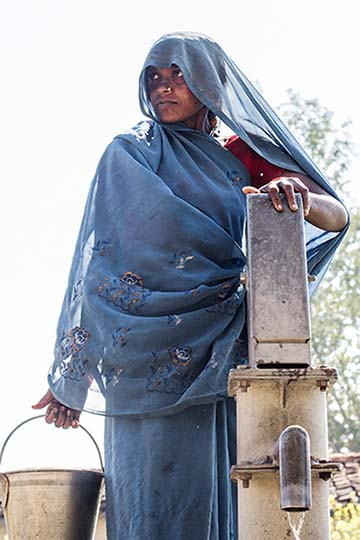 Indian woman next to a well
